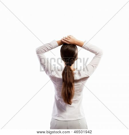 Image of young woman standing with her back with arms above head. Place for text