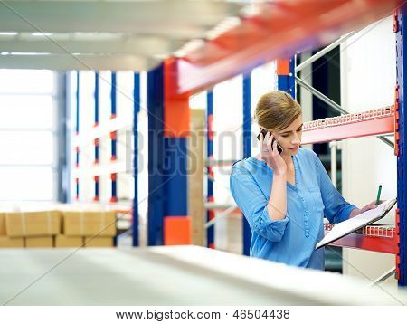 Businesswoman On The Phone And Checking Inventory In Warehouse