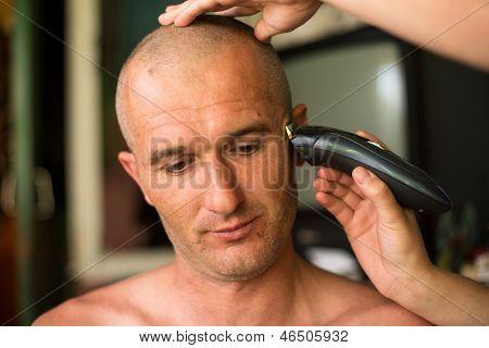 Hairdresser shaving man with hair trimmer.