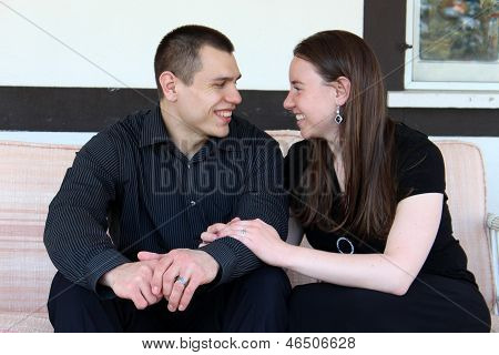 Young smiling couple on loveseat