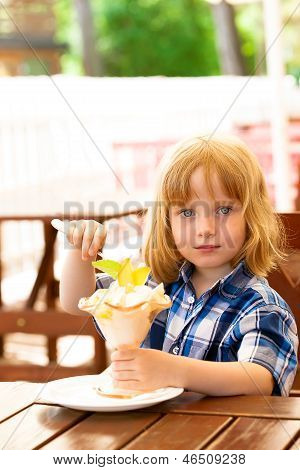 Small girl eating ice cream in cafe