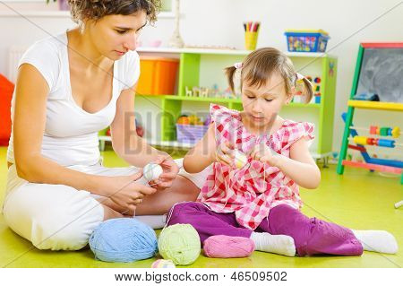 Young Mother And Little Daughter Decorating Easter Eggs