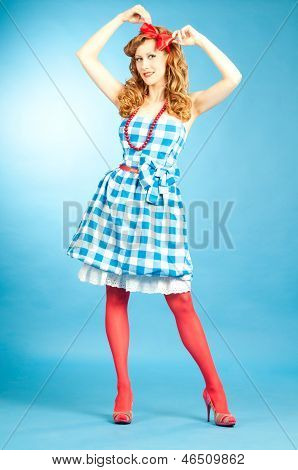 Pretty Sexy Redhead Pin Up Girl In  Checkered Dress And Red Stockings Adjusts The Bow On Her Head