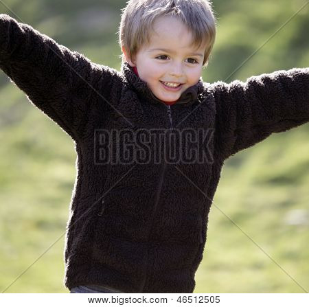 Young boy smiling and running with arms outstretched outdoors