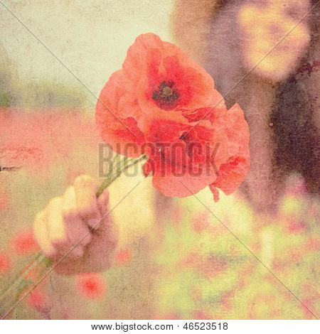 Young beautiful happy woman with bunch of poppy on field, summer outdoor. Vintage paper stylization, toned and texture added.