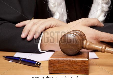 Referee gavel and a judge in judicial robes