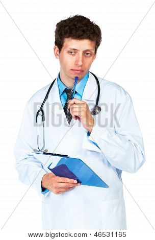 Portrait Of Deliberating Young Male Doctor Writing On A Patient's Medical Chart On White