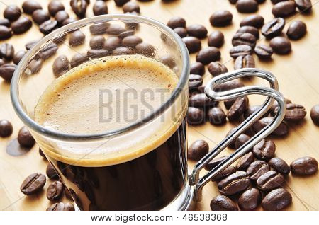closeup of a cup of coffee on a wooden table with roasted coffee beans