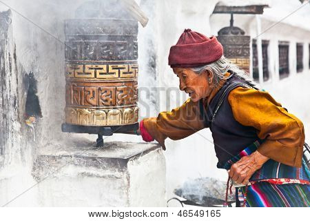 KATHMANDU, NEPAL - MAY 18: Unidentified woman go around one of the most significant relics in the world Bouddanath Stupa praying wheels May 18, 2013 in Kathmandu, Nepal.