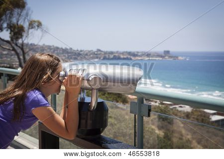 Young Girl Looking Out Over the Pacific Ocean and La Jolla, California with Telescope.