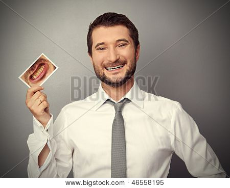 smiley healthy man holding picture with dirty yellow teeth