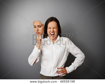 young businesswoman hiding her anger behind the mask of indifferent mood