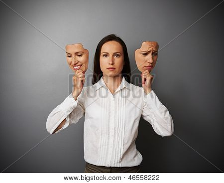 young businesswoman woman holding two masks with different mood