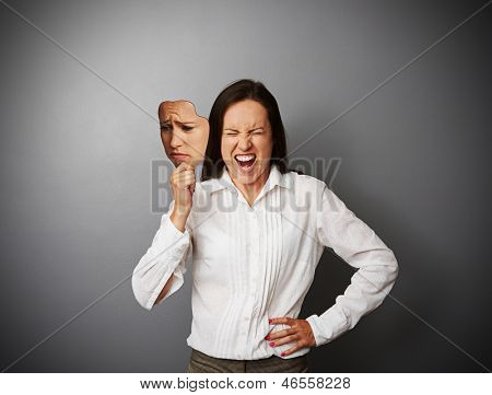 young businesswoman hiding her anger behind the mask of sad mood