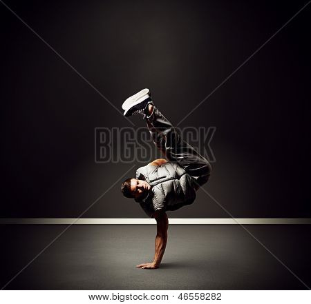 cool young dancer standing on the freeze over dark background