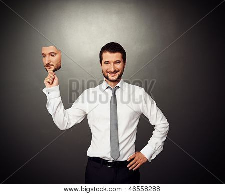smiley businessman holding serious mask over dark background