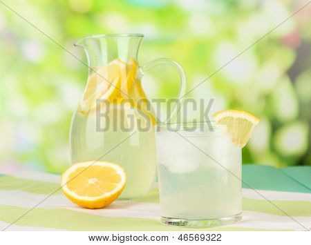 Citrus lemonade in pitcher and glasses on wooden table on natural background