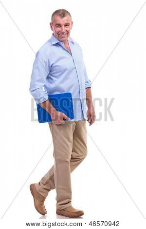 full length picture of a casual senior man standing with a clipboard in a hand and a pen in the other, while smiling for the camera. isolated on white background