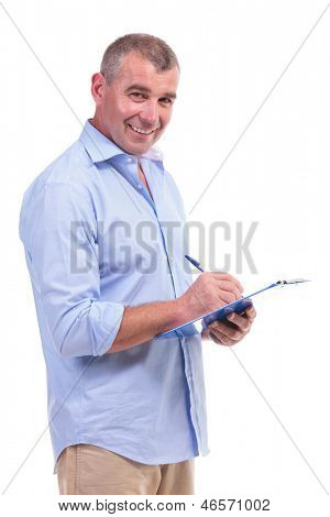casual senior man writing something on a clipboard while smiling at the camera. isolated on white background