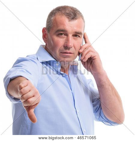 casual senior man talking on the telephone and showing the thumb down gesture while looking at the camera. isolated on white background