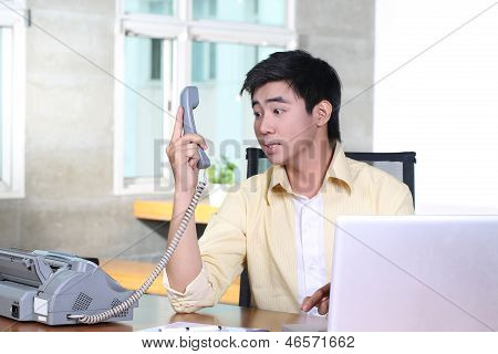 unhappy Asian business man on phone at desk with bad news