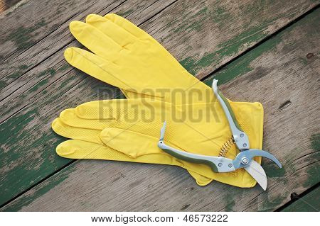 Yellow Rubber Gloves And Garden Pruner On Wooden Background.