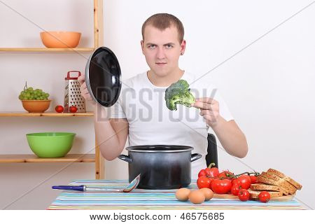 Young Man Cooking Soup In The Kitchen