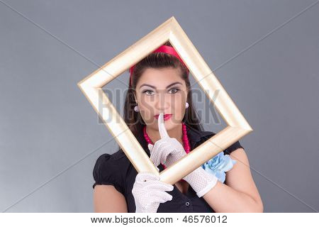 Pinup Girl With A Frame Around Her Face And Finger On Lips