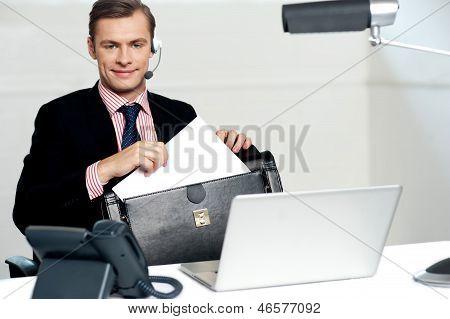 Männliche Call Centre Executive anordnen von Papierarbeiten