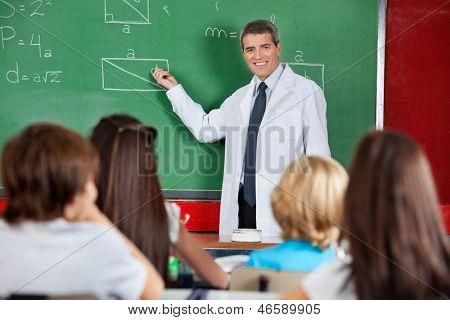 Mature male teacher teaching schoolchildren in classroom