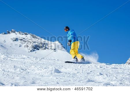 Man snowboarding down the snowy hill