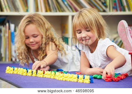 Two Elementary Pupils Counting Together In Classroom