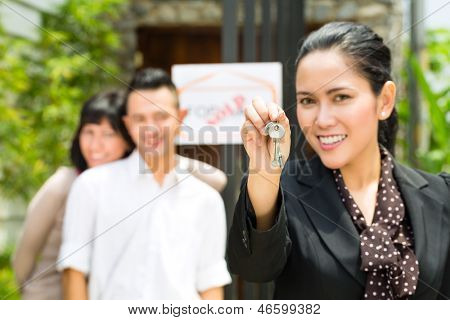 Real estate market - young Indonesian couple looking for real estate apartment or house to rent or buy, the realtor holding the keys