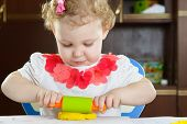 Cute Little Girl Rolling Clay Dough With