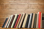 Old books on a wooden shelf. No labels, blank spine. poster