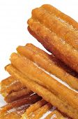 a pile of porras, thick churros typical of Spain, on a white background