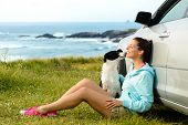 stock photo of petting  - Happy woman and dog sitting outside car on summer travel vacation - JPG