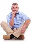 casual senior man sitting on the floor with his legs crossed and holding his hand at his chin, in a