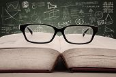 stock photo of hardcover book  - Pair of glasses and book in a classroom with written chalkboard - JPG