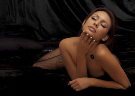 image of fishnet stockings  - Beautiful actress model in fishnet stockings lying on bed - JPG