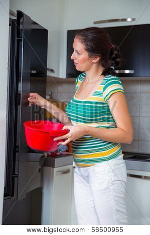 Woman in kitchen fixing dinner