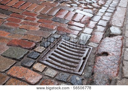 Wet Drainage Cover On Stone Pavement Of Urban Road