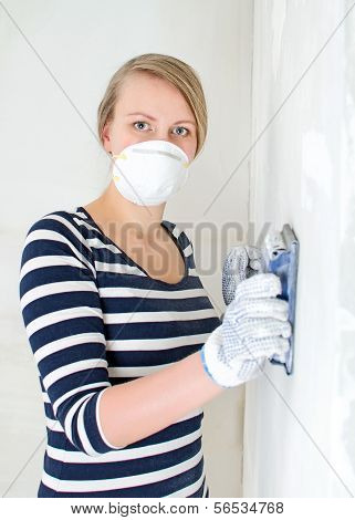 Female Plasterer Polishing The Wall.