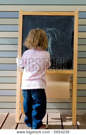 Cute Young Caucasian Boy Writing On A Blackboard