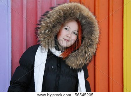 Girl In Hood With Fur Stands Near Multicolored Fence At Winter.