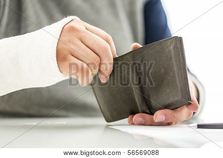 Mans Arm In A Plaster Cast Holding A Wallet
