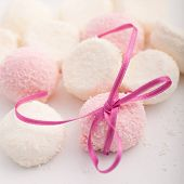 picture of dredge  - Pink and white marshmallows or confectionery dredged with coconut and displayed with a pretty pink bow close up view with shallow dof - JPG