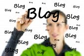 picture of marker pen  - Female blogger writing the word Blog on a virtual interface with a marker pen as she extols the importance of communication and networking with the social community via a blog or diary - JPG
