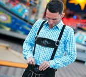 image of lederhosen  - Funny bavarian man checking his lederhosen trousers - JPG