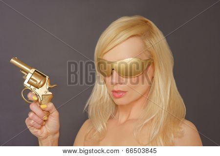 Girl With Blonde Hair wearing Gold shades Holding a Gun.